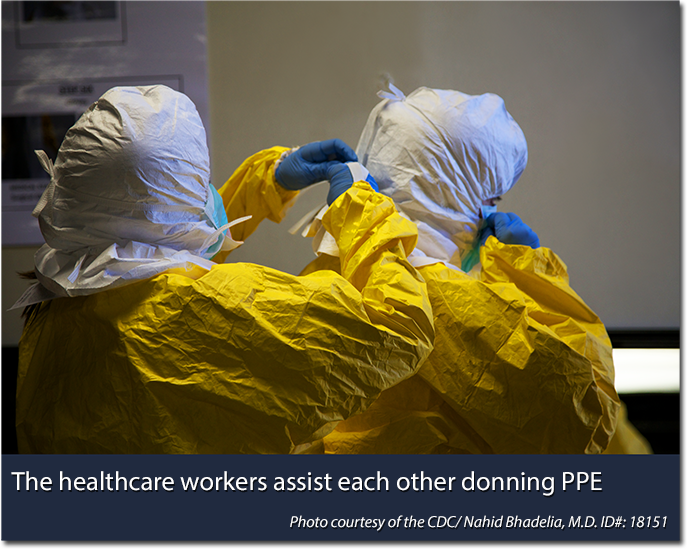 Healthcare workers assisting each other donning PPE. Photo courtesy of the CDC/Nahid Bhadelia, MD ID#: 18151